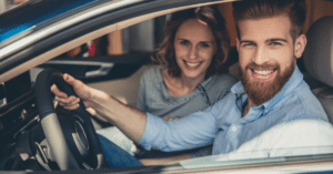 smiling couple looking out of a car buying a car vs leasing